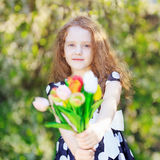 Little girl with bouquet of tulips. Stock Photos