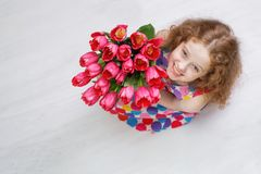 Little girl with bouquet of tulips. Royalty Free Stock Photography