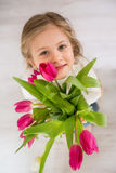Little girl with bouquet of tulips Stock Images