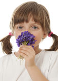 Little girl with a bouquet of violets Stock Images