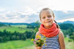 Little girl with a bouquet of wild flowers on a background of a. Smiling little girl with a bouquet of wild flowers on a background of a mountain landscape royalty free stock photos