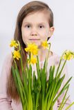 Girl with a bouquet of yellow daffodils stock image