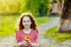 Little girl with bouquet of yellow dandelions in park. Royalty Free Stock Image