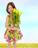 Little girl with a bouquet of yellow tulips. Royalty Free Stock Photos