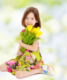Little girl with a bouquet of yellow tulips. Royalty Free Stock Images