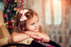 Little girl with bow at the Christmas tree sitting royalty free stock photos