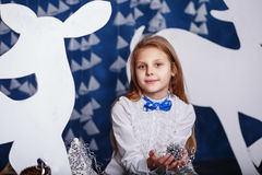 Little girl with bow-tie in christmas decorations. Royalty Free Stock Images
