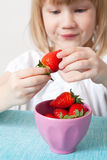 Little girl with a bowl of strawberries Stock Photo