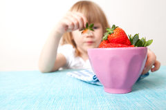 Little girl with a bowl of strawberries Stock Images