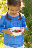 Little girl with a bowl of strawberries royalty free stock images
