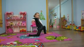 Little Girl Bows Down. Little caucasian white european 5 years old girl bows down in black penguin costume with pink bow tie in the children`s room stock video footage