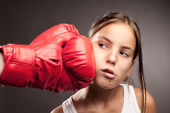 Little girl boxer. Little girl and red boxing globe  hitting her face Royalty Free Stock Images