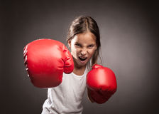 Little girl boxer. Little girl wearing red boxing gloves Royalty Free Stock Images