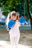 Little girl with boxing gloves. Girl with blue boxing gloves punching Stock Image