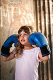 Little girl with boxing gloves. Girl with blue boxing gloves showing strength Royalty Free Stock Images
