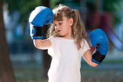 Little girl with boxing gloves. Girl with blue boxing gloves showing strength Stock Image
