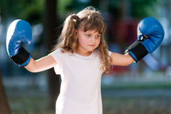 Little girl with boxing gloves. Girl with blue boxing gloves showing strength Stock Photo