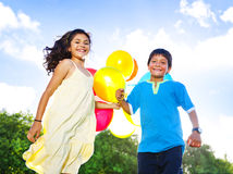 Little Girl And A Boy With Balloons Playing In The Park.  Stock Photos