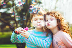 Little girl and boy blowing soap bubble. Stock Photos