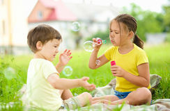 Little girl and boy are blowing soap bubbles Royalty Free Stock Photo