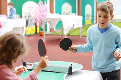Little girl and boy in blue play table tennis in park Stock Photo