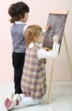 Little girl and boy draw by chalk ship in sea at chalkboard Stock Photos