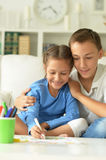 Little girl with boy drawing. At home Royalty Free Stock Photos
