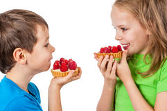 Little girl and boy eating cakes Royalty Free Stock Photography