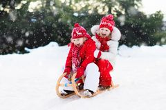 Kids on sleigh. Children sled. Winter snow fun. Little girl and boy enjoy a sleigh ride. Child sledding. Toddler kid riding a sledge. Children play outdoors in Royalty Free Stock Photography