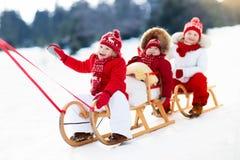 Kids on sleigh. Children sled. Winter snow fun. Stock Photo