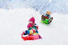 Kids play in snow. Winter sled ride for children. Little girl and boy enjoying sleigh ride. Child sledding. Toddler kid riding a sledge. Children play outdoors royalty free stock photos