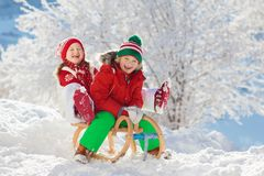 Little girl and boy enjoying sleigh ride. Child sledding. Toddler kid riding a sledge. Children play outdoors in snow. Kids sled. In snowy park in winter royalty free stock photos