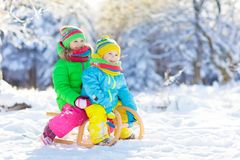Kids play in snow. Winter sled ride for children stock photos