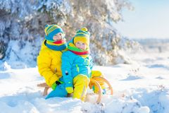Kids play in snow. Winter sled ride for children. Little girl and boy enjoying sleigh ride. Child sledding. Toddler kid riding a sledge. Children play outdoors stock photos