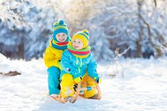 Kids play in snow. Winter sled ride for children. Little girl and boy enjoying sleigh ride. Child sledding. Toddler kid riding a sledge. Children play outdoors royalty free stock photo