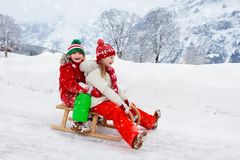 Little girl and boy enjoying sleigh ride. Child sledding. Toddler kid riding a sledge. Children play outdoors in snow. Kids sled. In snowy park in winter royalty free stock image