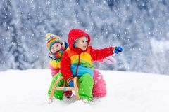 Kids play in snow. Winter sleigh ride for children. Little girl and boy enjoying sleigh ride. Child sledding. Toddler kid riding a sledge. Children play outdoors stock images