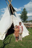 Little girl and boy in front of tee-pee Stock Photography