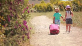 Little girl and boy go on the road with a case. Happy little girl and boy holding hands, go on the road with a case stock video footage