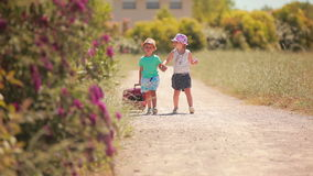 Little girl and boy go on the road with a case. Happy little girl and boy holding hands, go on the road with a case stock footage