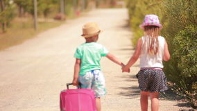 Little girl and boy go on the road  with a suitcase. Happy little girl and boy holding hands, go  on the road  with a suitcase stock footage