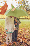 Little girl and boy hiding under an umbrella Stock Photos