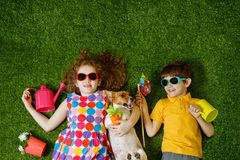 Little girl and boy, and his dog lying on green grass. Stock Photos