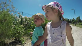 Little girl and boy holding hands, go on the road stock footage
