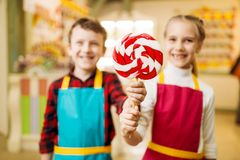Little girl and boy holds in hands fresh lollipop. Children in workshop at pastry shop learn to make handmade caramel. Holiday fun in candy store Royalty Free Stock Photos