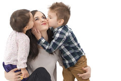 Little girl and boy kissing their mother on white Stock Photo