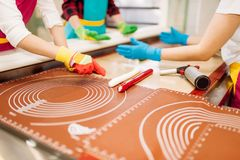 Little girl and boy learn to make caramel. Little girl and boy in workshop at pastry shop learn to make caramel. Holiday fun in candy store. Lollipop preparation Stock Image