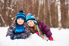 Little girl and boy lie nearby on snowdrift Stock Images