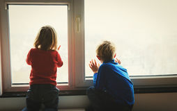 Little girl and boy looking through the window, waiting and expectation Royalty Free Stock Photos