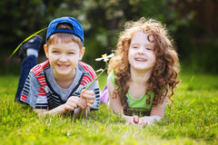 Little girl and boy lying on the green grass and smiling. Stock Image